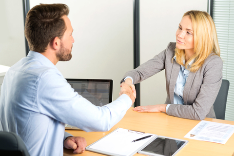 man and women in job interview shaking hands