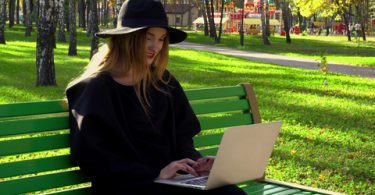 Happy young blogger with red lips in hat with wide brim and stylish coat typing outdoors on laptop in the autumn park