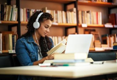 college student listening to music while studying in the library