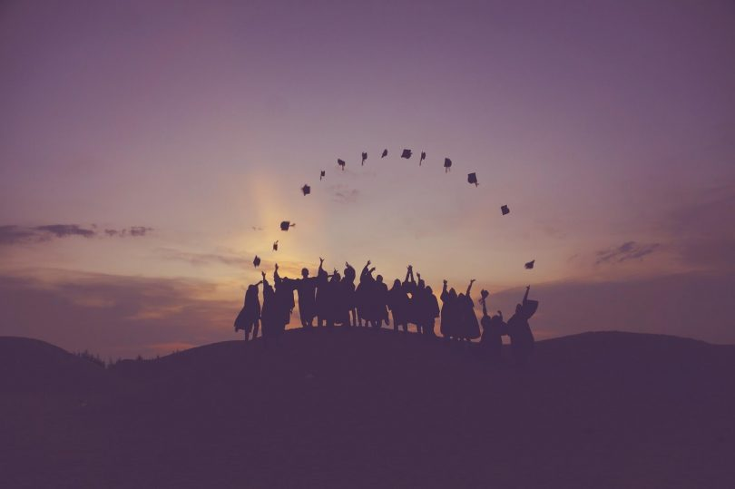 Silhouettes of college graduates on a hill horizon throwing their caps in the air