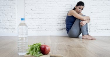 young woman sitting on ground alone and worried at home suffering from eating disorder