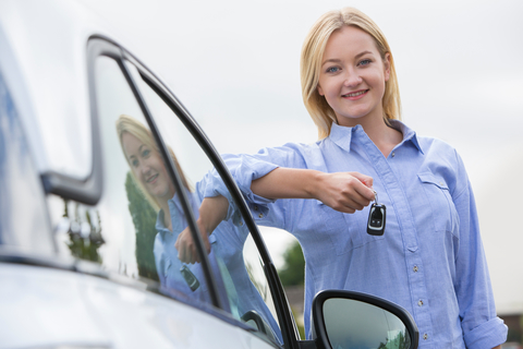 Young Female student Holding Car Keys Next To Vehicle