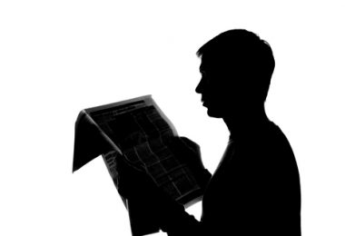 College student thoughtfully reading a newspaper - silhouett