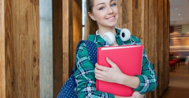 femail college students with head phones holding a red book