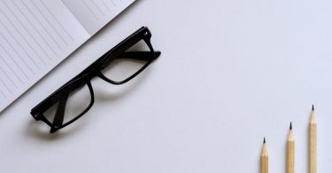 black glasses, notebook and pencils on a white desk