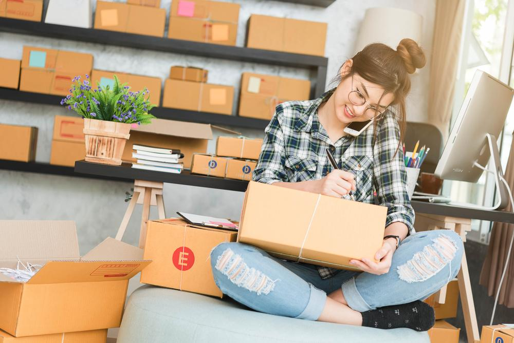 Asian Female college student writing on box while packing
