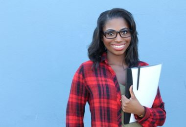 African american female college freshman holding books with a blue background
