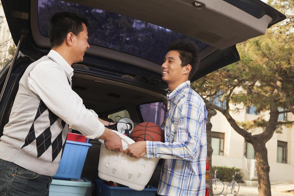 asian dad passing his son his belongings to pack into the car