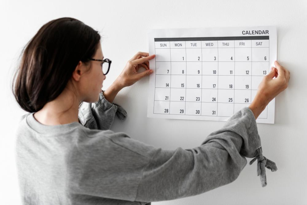 female college student hanging wall calendar