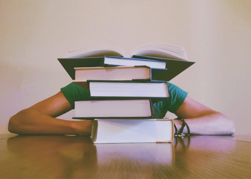 tired student sleeping behind a pile of books at a table
