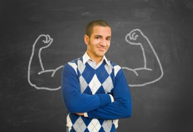 college student in blue sweater standning in front of chalk board with flexing muscles drawn on it