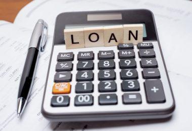 scrabble tiles spell loan on top of a calculator beside a pen on a desk