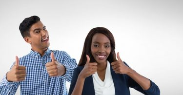 College Male and femal student giving a thumbs up in front of a white background