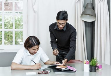 college studrnt teaching another student in home setting