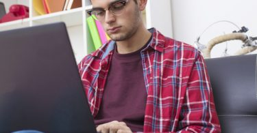male college student typing on laptop at home