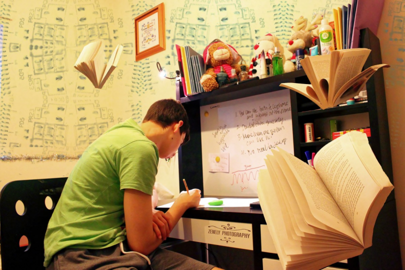 male college student in green shirt writing a paper at his desk