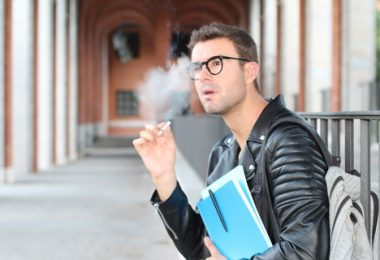 student wearing glasses sitting outside of school smoking while holding his books
