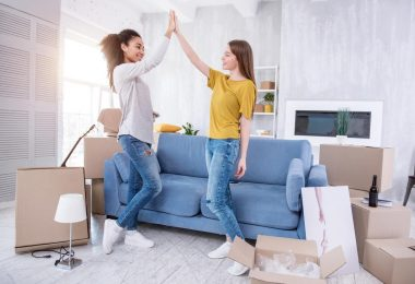 tweo female college roommates doing high five in their new home
