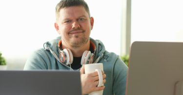 smiling male student using online education service and drink tea or coffee.