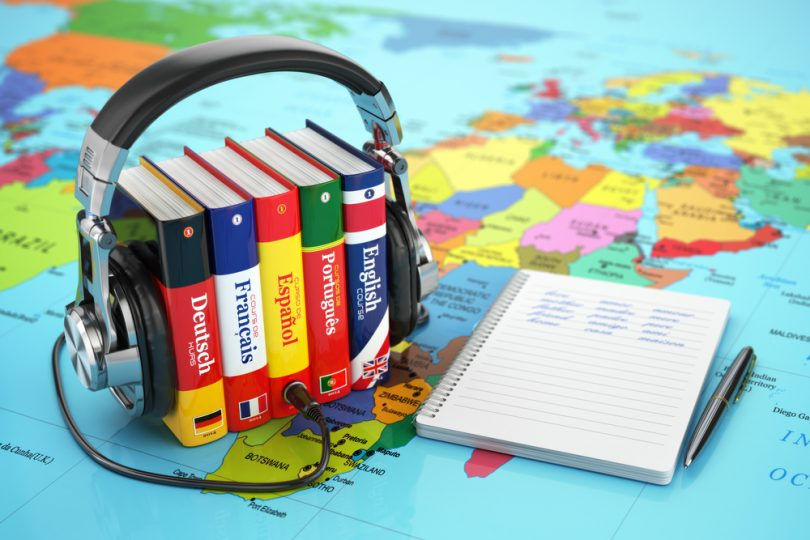 headphones wrapped around textbooks, sitting on a colorful map
