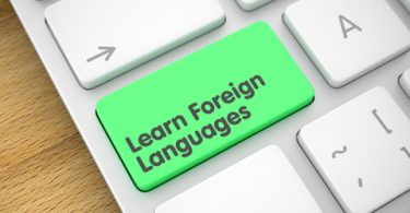 Learn Foreign Languages on Slim Aluminum Keyboard lying on the Wood Background.