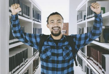 Picture of African male college student celebrating his success by lifting hands in the library