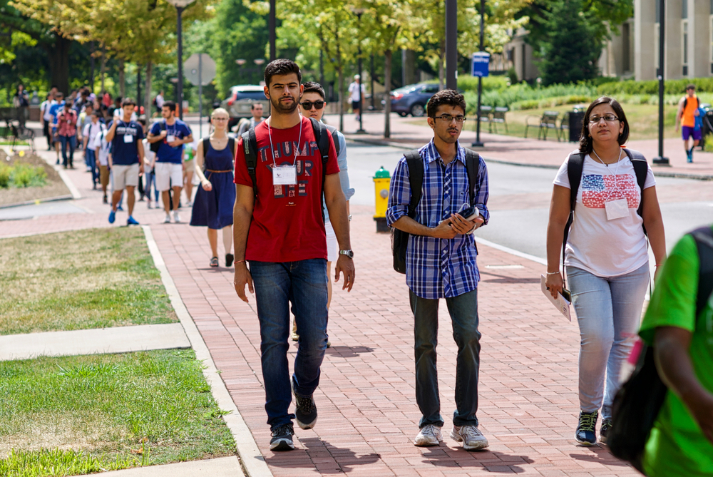 Many college student walking on the sidewalk on a sunny day