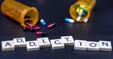 scrabble letters laid out on table spelling out the word addiction with pills spilled out of their containers in the background.