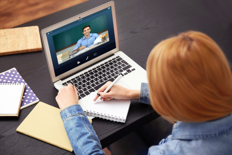female college student with red hair on laptop doing an online course at her desk