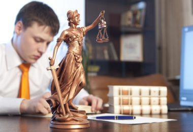 Justice statue and law student studying a book at his desk