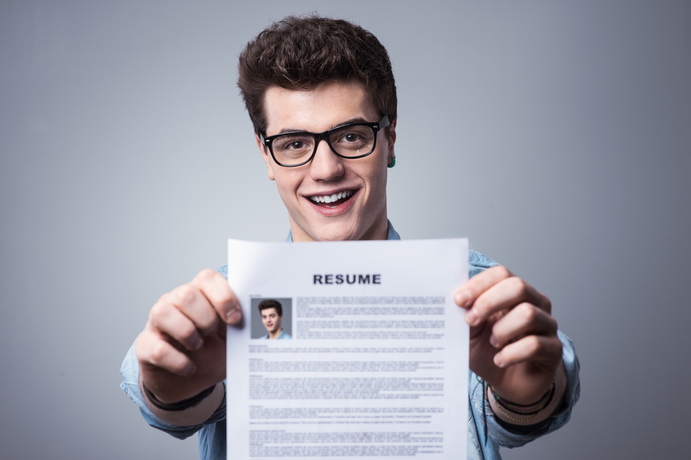Male college student holding up a resume