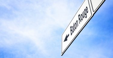 White signboard with an arrow pointing left towards Baton Rouge, Louisiana, USA, against a hazy blue sky in a concept of travel, navigation and direction. Path included for the signboard