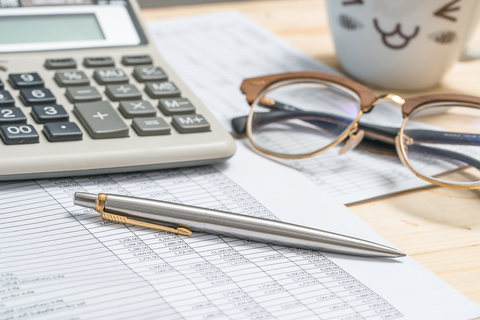 Accounting tools on a desk with calculator, pen glasses and coffee mug