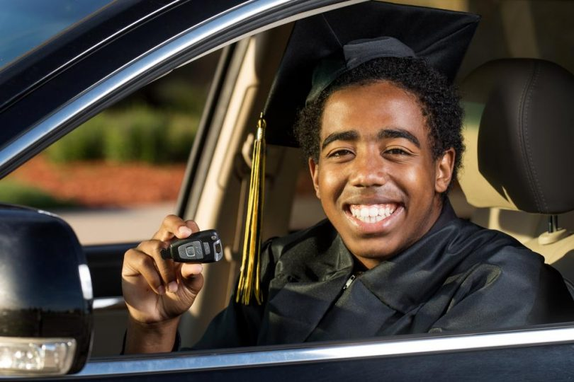 young male college graduate sitting in his first car holding his keys and smiling
