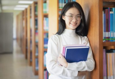 smiling female asian college student holding her books and standing in the library