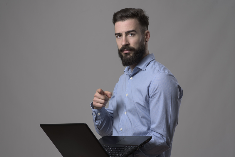 young entrepreneur student in blue shirt holding laptop and pointing