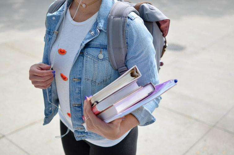 female college student standing outside wearing backpack and holding textbooks