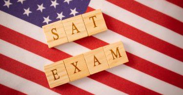 Wooden tiles that spell SAT EXAM on american flag
