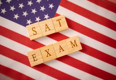 Wooden tiles that spell SAT EXAM on american flag