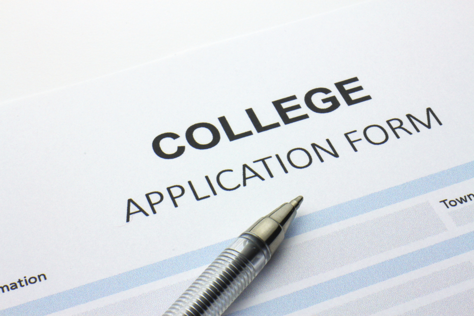 college application form with a pen sitting on top of it