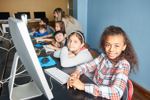 Group of kids learn computer science in a computer class of elementary school
