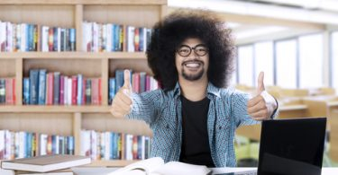 Picture of an Afro college student looks happy while showing thumbs up in the classroom