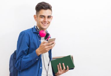 college adolescent student with books and mobile phone on wall background