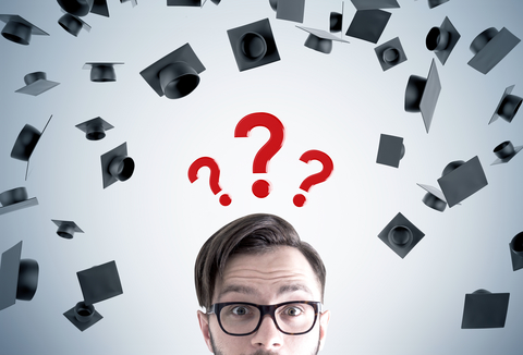 Close up of a young mans head. He is wearing glasses and standing near a gray wall with graduation hats and three question marks above his head