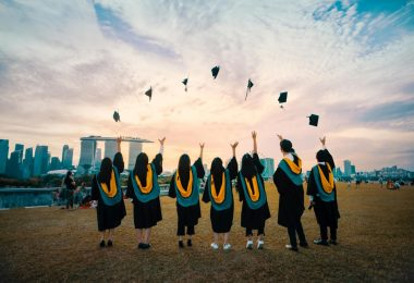 college graduates throwing their hats in the air outside