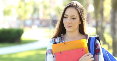 Front view portrait of a sad student walking in the street holding folders outdoors in a park