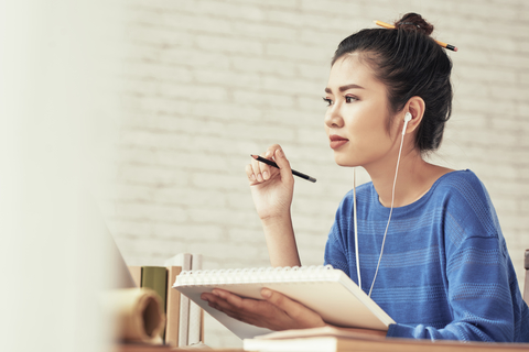 Smart Asian girl with pencil in hear writing essay