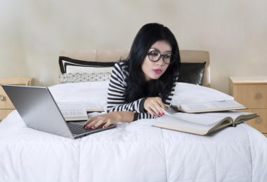 Portrait of beautiful female college student writing an essay using a laptop computer on the bed