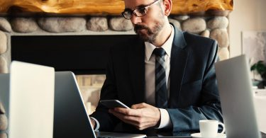 Business student on laptop with cell phone in hand