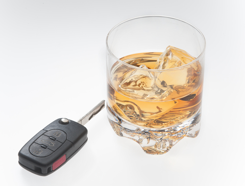 car key and alcoholic beverage with ice in a glass sitting on white background